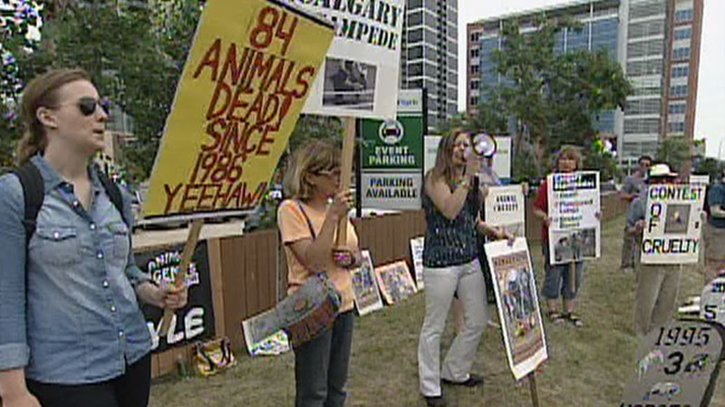 Protesters hold signs outside of the Calgary Stampede grounds in Calgary, Saturday, July 14, 2012.