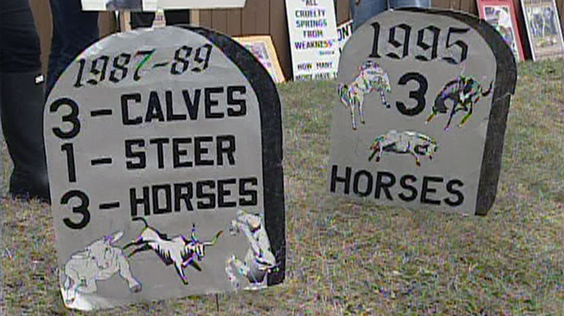Signs shaped like gravestones stand in front of protesters in Calgary, Saturday, July 14, 2012.