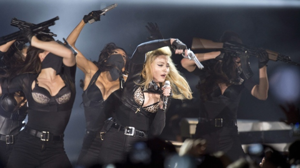 Madonna performs with a gun on stage during her concert in Cologne, Germany on July 10, 2012.