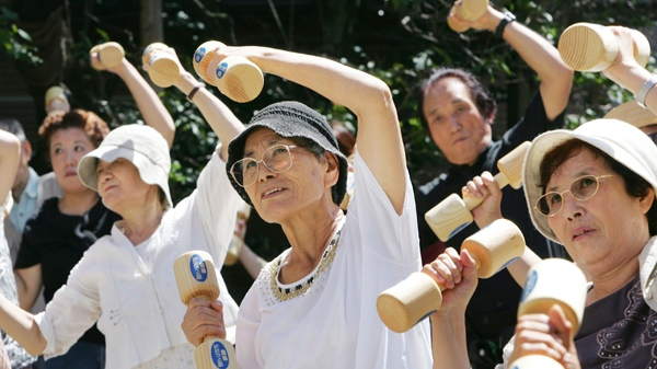 Elderly people use pairs of wooden dumbbells to exercise during a health promotion event at a Tokyo temple on Respect the Aged Day, Monday, Sept. 17, 2007. (AP / Koji Sasahara)