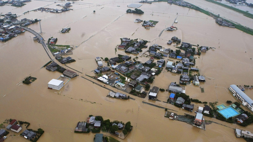 Houses are half submerged after water broke Yabe River's embankment, top, in Yanagawa, Fukuoka Prefecture, Japan, Saturday, July 14, 2012. (AP / Kyodo News)