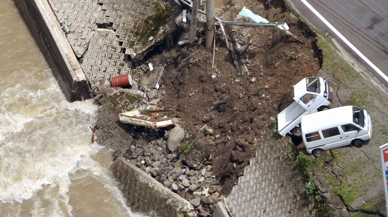 A road along a river is partially collapsed in Yame, Fukuoka Prefecture, Japan, Sunday, July 15, 2012. (AP / Kyodo News)