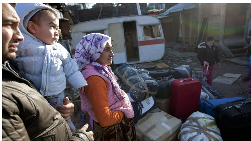A family stand by their packaged belongings in the Casilino 900 gypsy camp in Rome, Friday, Jan. 22, 2010. (AP Photo / Andrew Medichini)