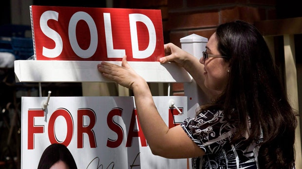 A real estate agent puts up a 'sold' sign in front of a house in Toronto.
