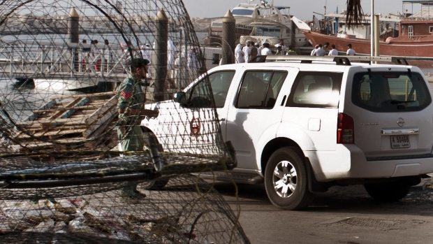 Emirati police and other officials inspect a boat