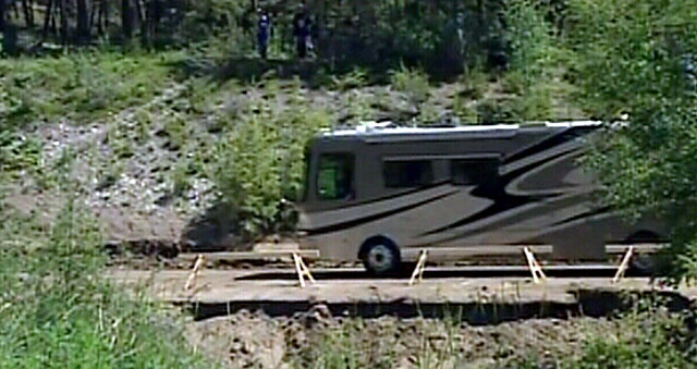 A recreational vehicle travels along a temporary access road, leaving the campgrounds at Fairmont Hot Springs Resort following a landslide that took out a bridge, trapping campers. July 16, 2012.