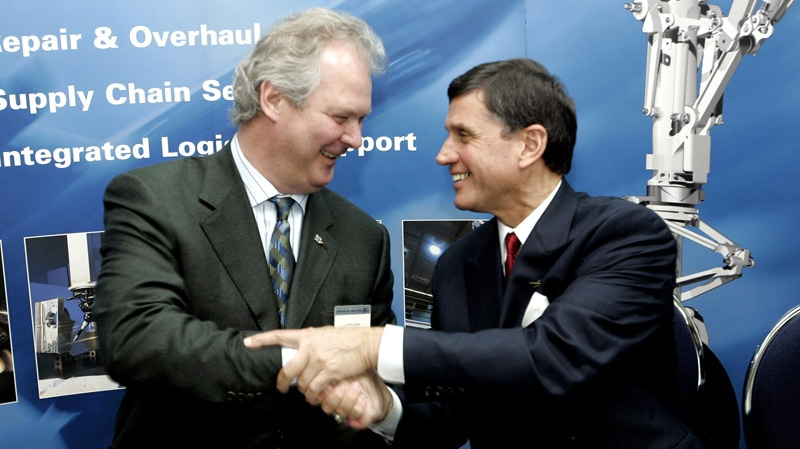 Gilles Labbe of Heroux-Devtek, left, and Ron Covais of Lockheed Martin shake hands.