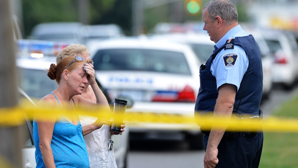 Civilians speak to the police near the scene of a shooting on Danzig Street where 23 people were injured and 2 confirmed dead at an outdoor barbecue on Tuesday July 17, 2012 . (Aaron Vincent Elkaim / THE CANADIAN PRESS)