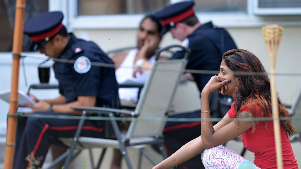 Police interview neighbours near the scene of a shooting on Danzig Street where 23 people were injured and 2 confirmed dead at an outdoor barbecue on Tuesday, July 17, 2012. (Aaron Vincent Elkaim / THE CANADIAN PRESS)