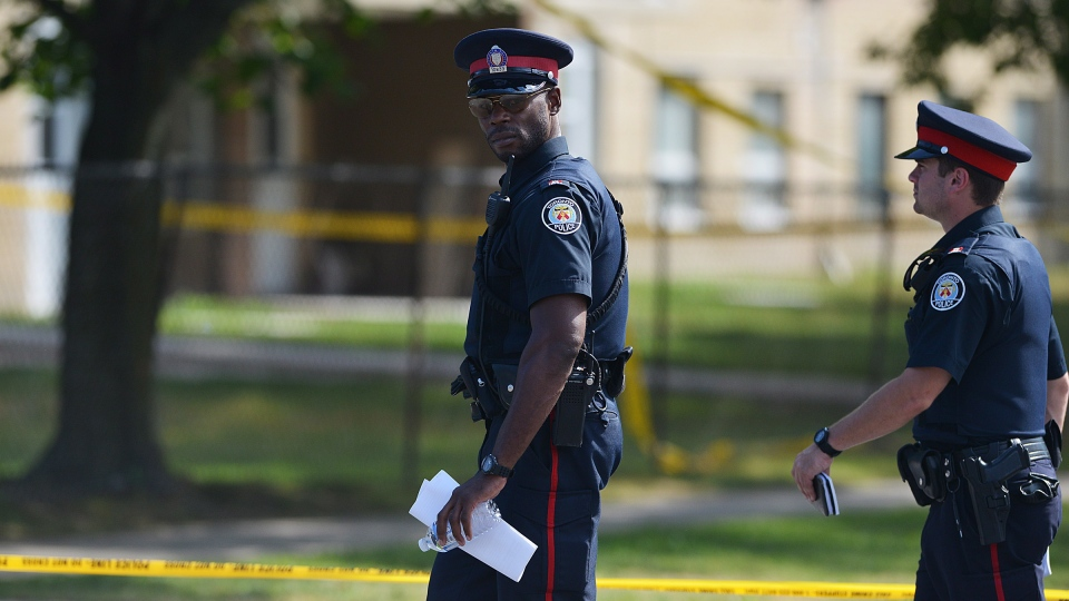 Toronto police investigate on Danzig Street near the scene of a shooting where 23 people were injured and 2 confirmed dead at an outdoor barbecue on Tuesday, July 17, 2012 . (Aaron Vincent Elkaim / THE CANADIAN PRESS)