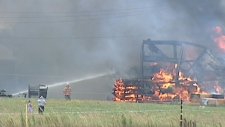 Firefighters battle a blaze at a woodworking shop north of Elmira, Ont.