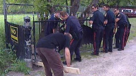 Officers and officials remove the Hells Angels clubhouse gate on July 29, 2010.