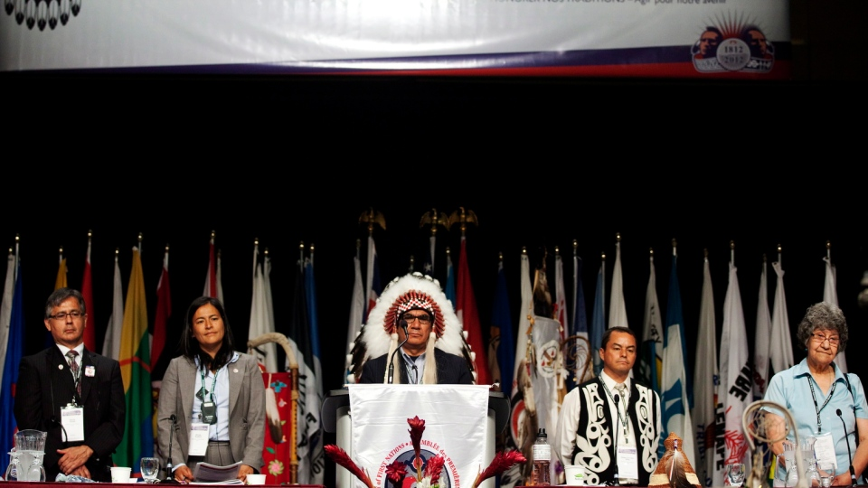 A panel of speakers stand as the opening ceremonies conclude during The Assembly of First Nations Annual General Assembly in Toronto on July 17, 2012. (Michelle Siu / THE CANADIAN PRESS)