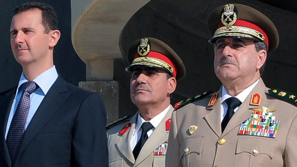 Syrian President Bashar Assad, left, stands next to Syrian Defense Minister Gen. Dawoud Rajha, right, during a ceremony to mark the 38th anniversary of the October 1973 Arab-Israeli war, in Damascus, Syria, Thursday Oct. 6, 2011. (SANA)