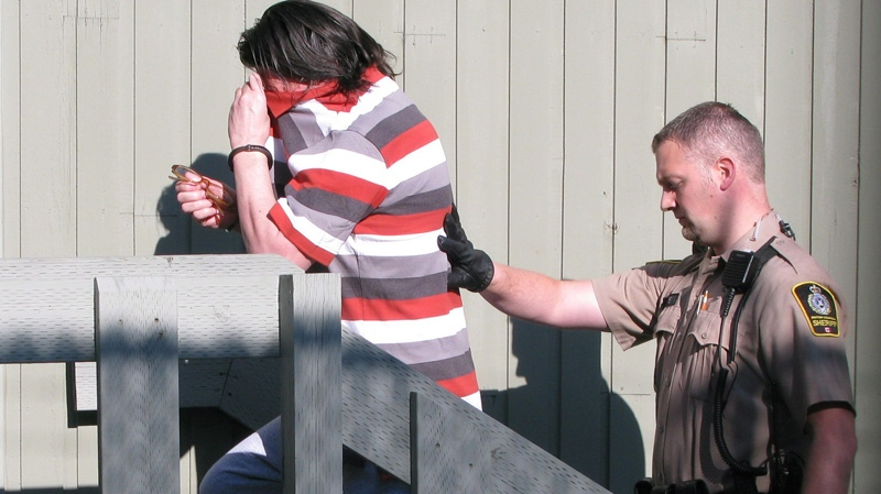 Randall Hopley covers his face as he is taken into his sentencing hearing the courthouse in Cranbrook, B.C. on Wednesday, July 18, 2012. (Bill Graveland / THE CANADIAN PRESS)