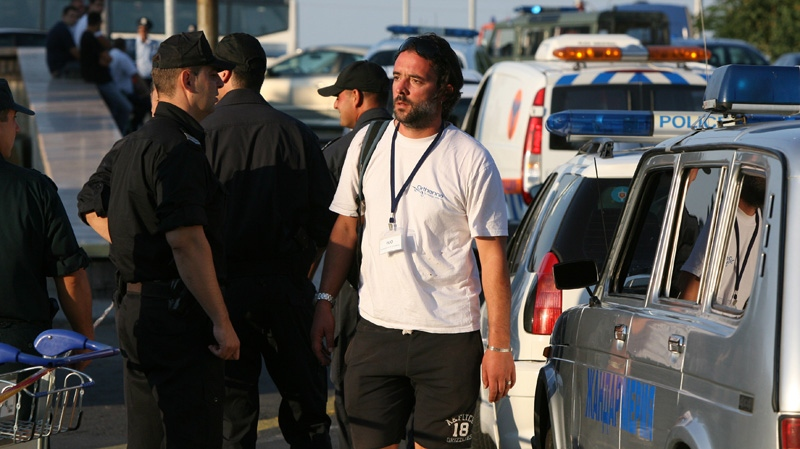 A tourist agency employee reacts as he passes by Bulgarian policemen shortly after a bomb attack against Israeli tourists near Burgas airport, outside the Black Sea city of Burgas, Bulgaria, some 400 kilometres east of the capital, Sofia on Wednesday, July 18, 2012.  (AP / Impact press Group)