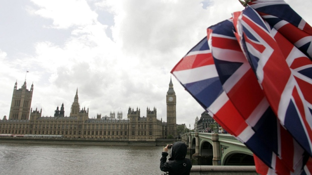 Union flags are seen at a souvenir shop as a tourist takes photographs of the Houses of Parliament in London, England, Monday, May 18, 2009. (AP / Akira Suemori)