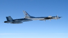 A CF-18, left, from 4 Wing Cold Lake flies next to a Russian Tu-95 'Bear' long-range strategic bomber on Sept. 5, 2007. (Department of National Defence)