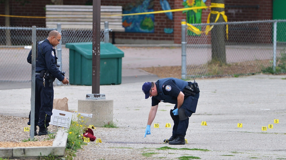 Police examine the scene of a shooting that took place early Thursday morning at a school yard in the Lawrence Heights area of Toronto on Thursday, July 19, 2012. (Aaron Vincent Elkaim / THE CANADIAN PRESS)