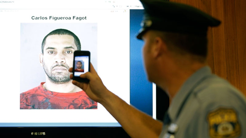 A police officer snaps an image with his phone of a booking photo of Carlos Figueroa-Fagot before a news conference in Philadelphia, Thursday, July 19, 2012. (AP / Matt Rourke)