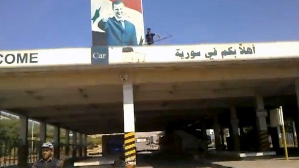 This image purports to show a Syrian rebel defacing a picture of President Bashar Assad at the Bab al-Hawa border crossing with Turkey, Thursday, July 19, 2012. (Shaam News Network via AP video)