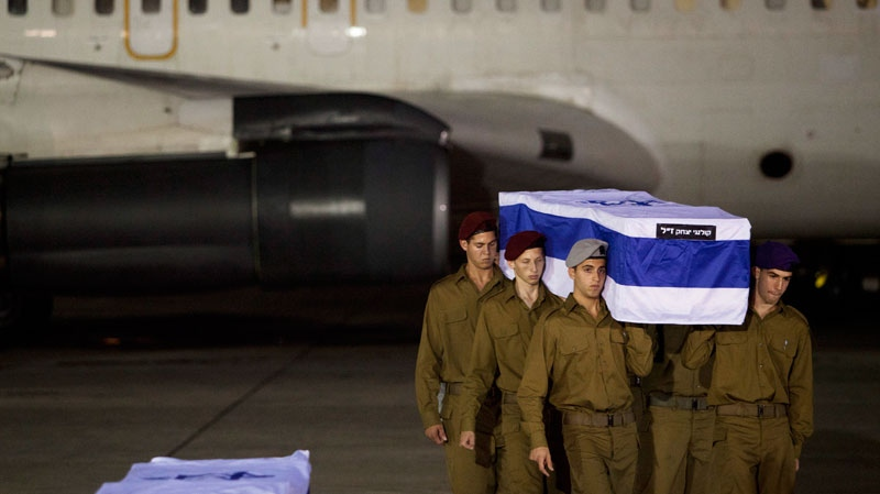 Israeli soldiers carry a coffin of victims killed in bombing in Bulgaria after the remains arrived at Tel Aviv airport, Israel, Friday, July, 20, 2012. (AP / Dan Balilty)