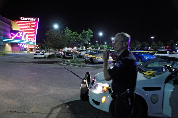 An Aurora Police officer talks on his radio outside of the Century 16 theater at Aurora Mall