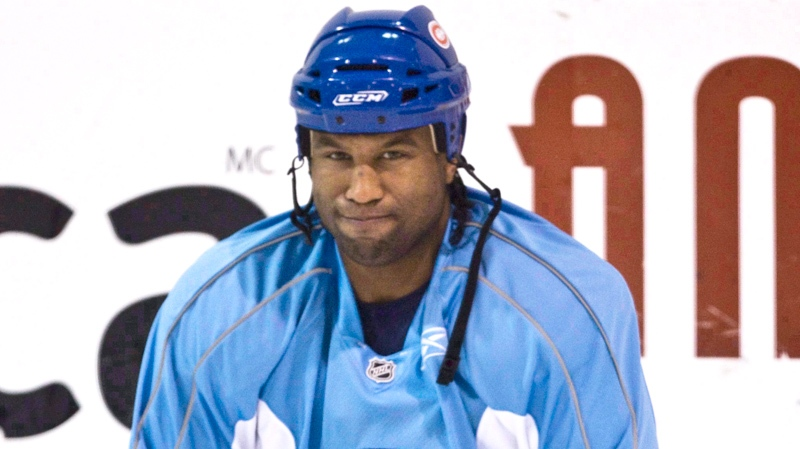 Georges Laraque stretches during a practice in Brossard, Que., Tuesday, April 14, 2009. (Paul Chiasson / THE CANADIAN PRESS)