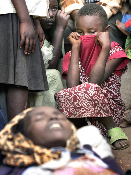 A young girl pulls her shirt over her mouth as she and other displaced Kenyans gather around the body of a woman at a makeshift camp housing those who had previously fled their nearby villages, in Noigam Primary School in Kachibora village, Kenya Sunday, Jan. 6, 2008. (AP Photo / Ben Curtis)