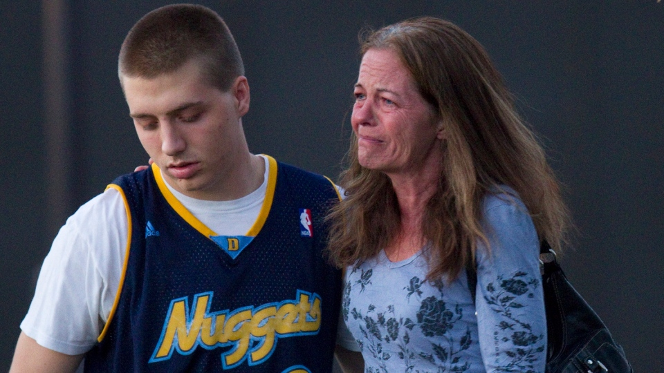 Eyewitness Jacob Stevens, 18, hugs his mother Tammi Stevens after being interview by police outside Gateway High School where witnesses were brought for questioning Friday, July 20, 2012 in Aurora, Colo. (AP / Barry Gutierrez)