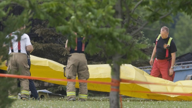 Firemen set up a yellow tarp near the crash site of an Aeropro Beechcraft King Air 100 in Quebec City, Wednesday June 23, 2010. The Beechcraft crashed shortly after take off near the airport. (Francis Vachon / THE CANADIAN PRESS)