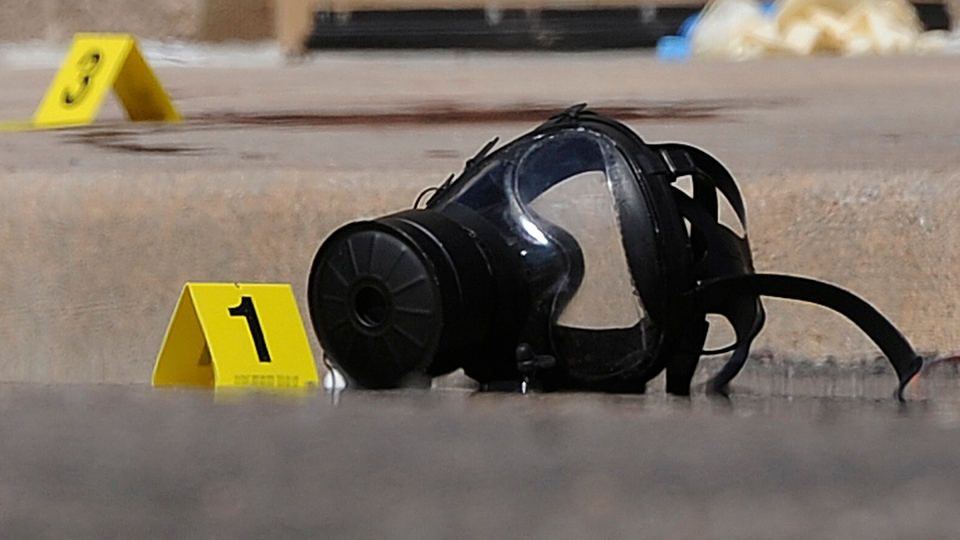 A gas mask was marked as the first piece of evidence in a criminal investigation outside the parking lot behind the Century 16 theatre after the shooting, Friday, July 20,2012. (The Denver Post / Karl Gehring)