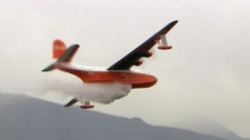 A water bomber flies past a wildfire burning out of control in Kelowna, B.C.