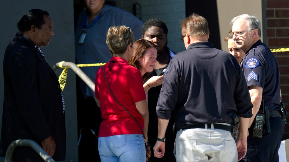 A woman overcome with emotion is surrounded by councilors, police and clergy outside Gateway High School where witnesses are being interviewed by authorities in Aurora, Colo., Friday, July 20, 2012. (AP / Barry Gutierrez)