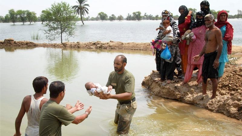 Pakistan army soldiers pass a baby across a water course as they help people flee from their flooded village following heavy monsoon rains in Taunsa near Multan, Pakistan, on Sunday, Aug. 1, 2010. (AP / Khalid Tanveer)