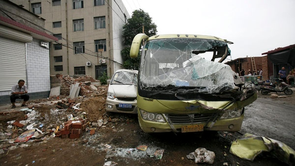 A man smokes near smashed vehicles at Yuanshi county, in north China's Hebei province, after a drunken shovel loader driver went on a rampage in northern China, smashing into shops and vehicles and killing 11 people on Sunday, Aug. 1, 2010. (AP Photo)