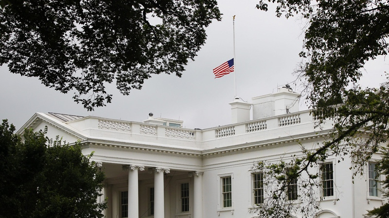 The American flag is seen at half-staff over the White House in Washington, Friday, July 20, 2012. (AP Photo/Pablo Martinez Monsivais)