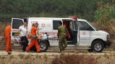 Israeli soldiers and medics carry an Israeli soldier, injured during an exchange of fire with Lebanese troops, out of an ambulance to a helipad to be transported to hospital, near the northern Israeli town of Kiryat Shmona, Tuesday, Aug. 3, 2010. (AP / Hamad Almakt)