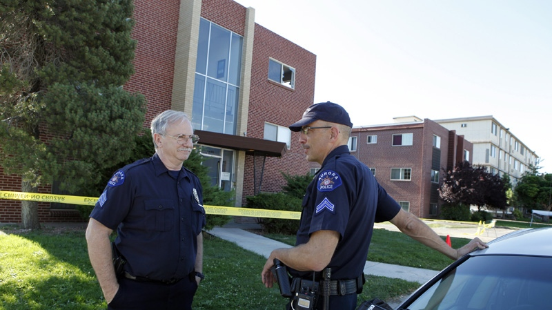 Aurora police officers Gary Reno, left, and Douglas Kasten stand guard at the apartment complex of shooting suspect James Eagen Holmes in Aurora, Colo. on Sunday, July 22, 2012. (AP / Ed Andrieski)