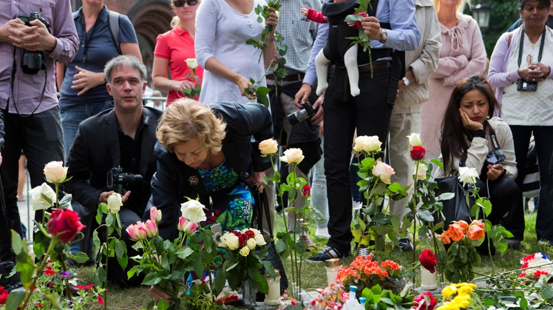 People lay down flowers outside the cathedral on the first anniversary of a bombing and shooting rampage in Oslo and on Utoya Island in Oslo, Norway on Sunday, July 22, 2012. (AP /Berit Roald/NTB scanpix)