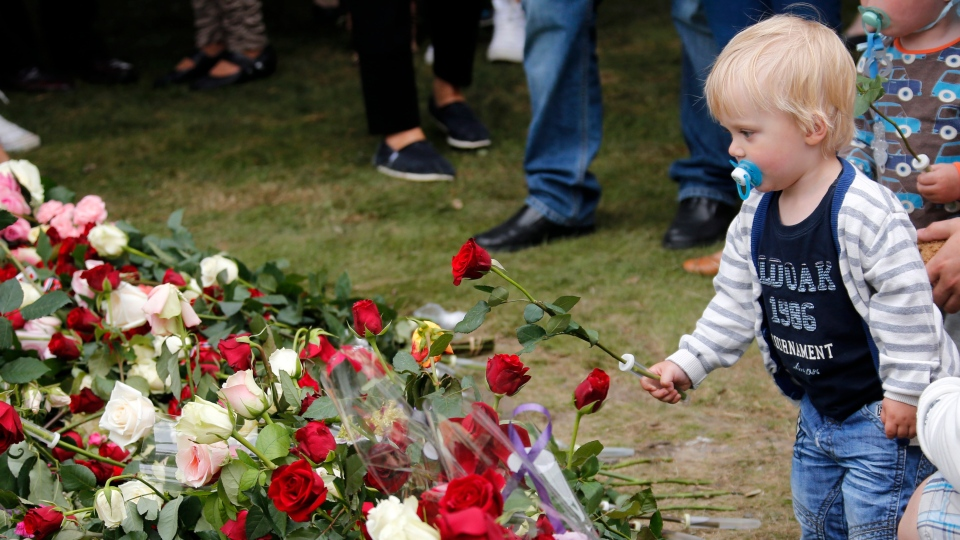 Theodor Christopher Jaeger Lindhjem, 2 years-old from Oslo, lays down a flower outside the cathedral in Oslo Sunday July 22, 2012. (AP / Lise Aserud / NTB scanpix)