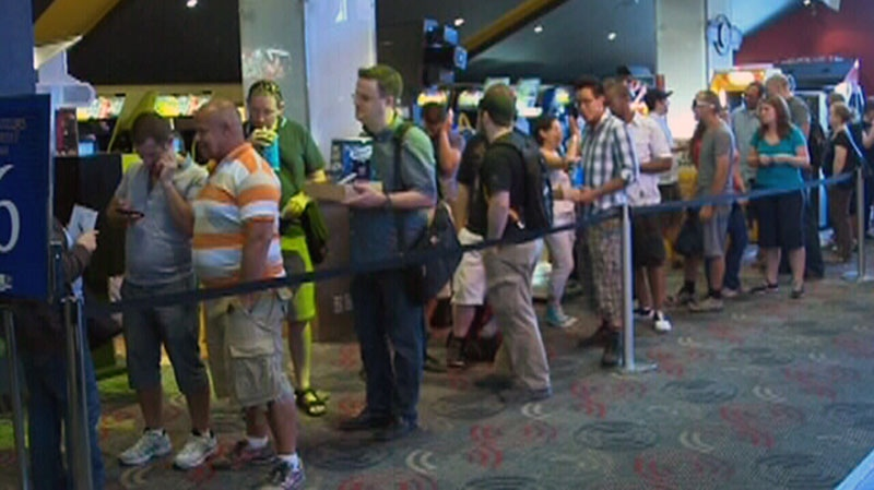 People line up outside of the theatre to watch 'The Dark Knight Rises' in this photo from video in Montreal, July 20, 2012.