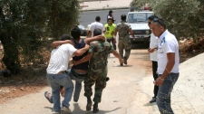 People carry an injured man after an exchange of fire between Israeli and Lebanese troops along the border between Israel and Lebanon, in the southern border village of Adaisseh, Lebanon, Tuesday, Aug. 3, 2010. (AP / Ronith Daher)