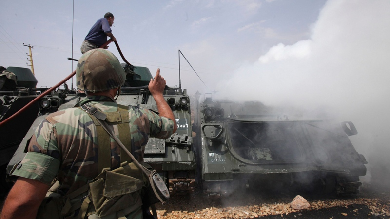 A Lebanese civil defense worker extinguishes a burning armored vehicle at a Lebanese army base in the southern border village of Taibeh, Lebanon, Tuesday, Aug. 3, 2010. (AP)