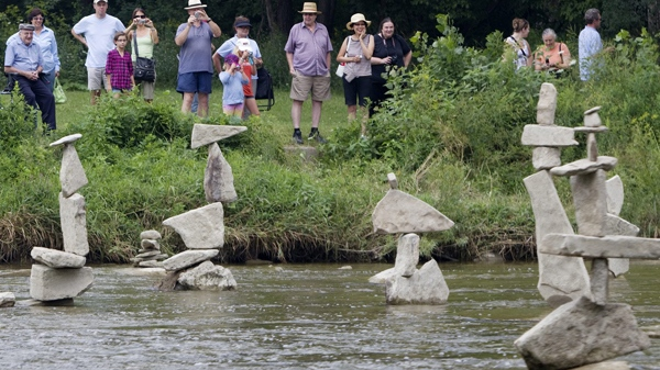 A crowd of people gather on the bank of the Humber River in Toronto, to look at balancing rock statues created by artist Peter Riedel, Tuesday, Aug. 3, 2010. (Darren Calabrese / THE CANADIAN PRESS)