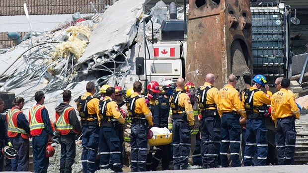 Rescue workers remove their hard hats as firefighters carry a second body out of the Algo Centre Mall in Elliot Lake, Ont., on Wednesday, June 27, 2012, after the mall's roof collapse. (Nathan Denette / THE CANADIAN PRESS)