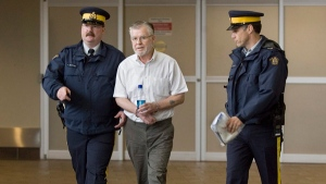 Ernest Fenwick MacIntosh is escorted in custody by RCMP officers at Robert L. Stanfield International Airport in Halifax on Thursday, June 7, 2007. (Andrew Vaughan / THE CANADIAN PRESS)