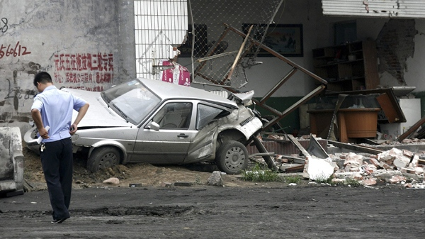 n this photo taken Sunday, Aug. 1, 2010, a policeman walks near a smashed car and shop at Yuanshi county, in north China's Hebei province. (AP Photo)