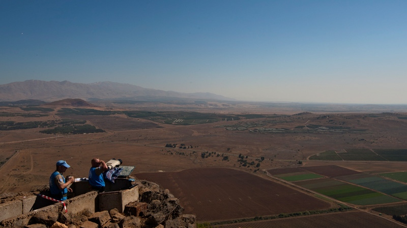 UN soldiers observe from an old army post from the 1967 war at Mt. Bental in the Golan Heights, overlooking Syria, Monday, July 23, 2012. (AP / Sebastian Scheiner)