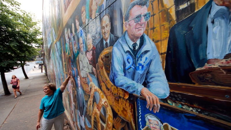 A woman touches a mural in downtown State College, Pa., featuring former Penn State head football coach Joe Paterno, center, on Monday, July 23, 2012.  (AP / Gene J. Puskar)